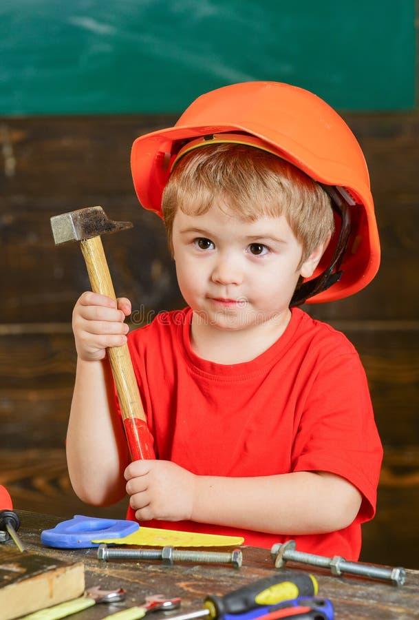 Closeupunge i orange hjälminnehavhammare i hans händer Tillverkar kurs på dagiset Stående av pysen in royaltyfri bild