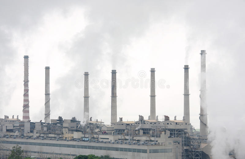 Closeview of thermal power chimneys with smokes stock image