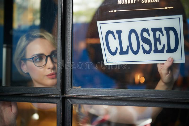 Closing store. Pretty young shop owner turning closed sign stock photo