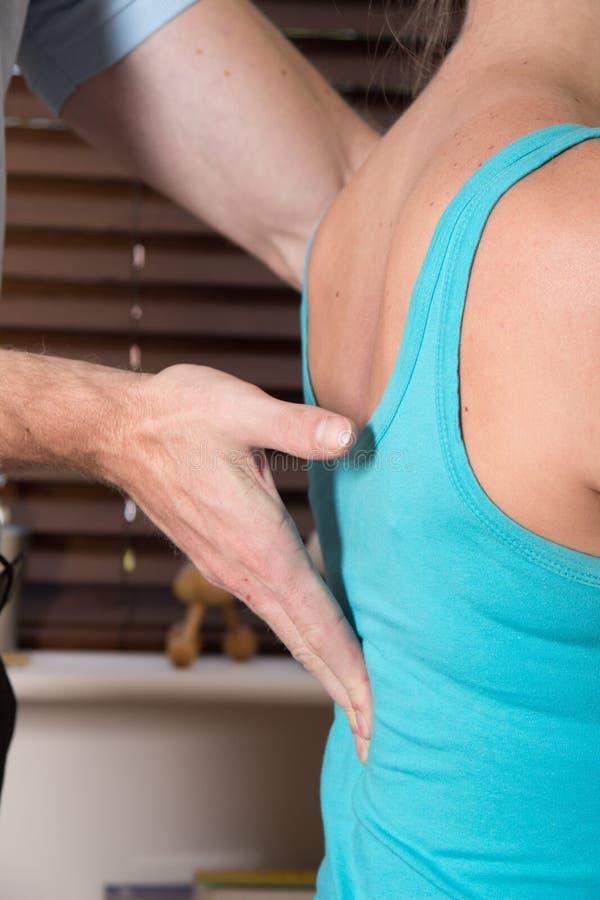 Closup della spina dorsale paziente femminile della mano del chiropratico fotografia stock libera da diritti
