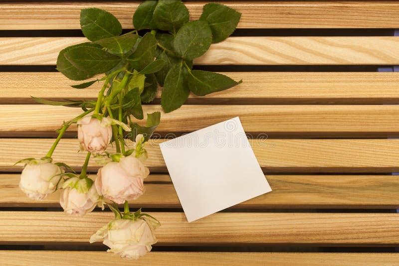 Closup do ramalhete da rosa do rosa e nota da etiqueta em um banco de madeira fotografia de stock