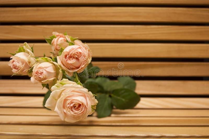 Closup för rosa färgrosbukett på en träbänk royaltyfri fotografi