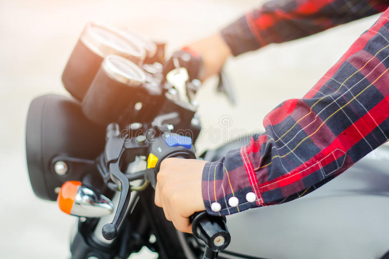 Closup hand men wear a red plaid shirt, Drive a vintage motorcycle. Closup hand men wear a red plaid shirt, Drive a vintage motorcycle royalty free stock images