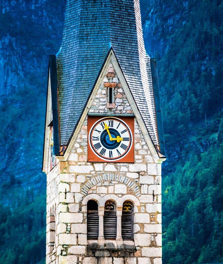 Closupmening van de klok van de protestantse kerk op hoge toren in Hallstatt, Oostenrijk stock foto's
