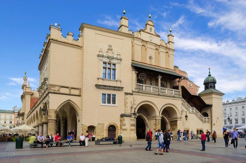 Cloth Hall (Sukiennice) in Cracow, Poland. CRACOW, POLAND - AUGUST 16, 2014: Tourists visiting the main market square in Cracow (Poland), which is one of the royalty free stock photography