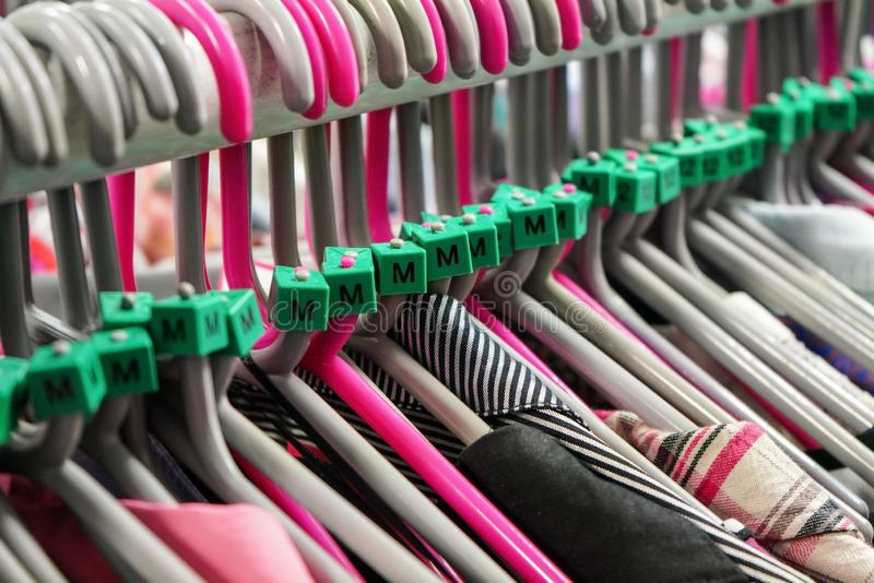 Cloth hangers with various women clothing in thrift shop, detail on M size marks.  stock photos