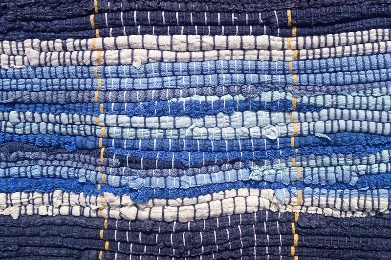 Cloth sewn from strips of fabric. Needlework, reuse of materials. Blue strips in a marine style. royalty free stock photos