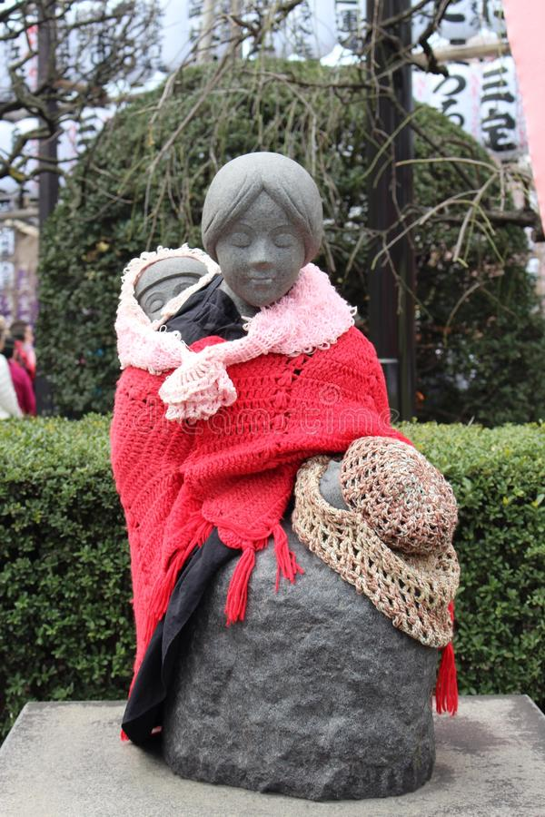 A clothed statue of mother and child near Asakusa Shopping Street Tokyo Japan. Keeping warm clothed statue Tokyo stock image
