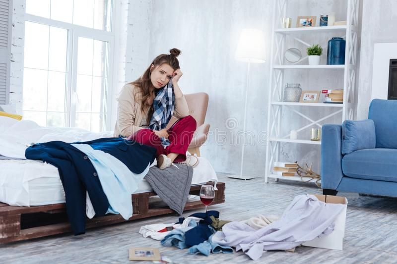 Emotional woman throwing clothes of ex boyfriend. Clothes away. Emotional depressed woman throwing all of the clothes of ex boyfriend away after his betrayal royalty free stock image