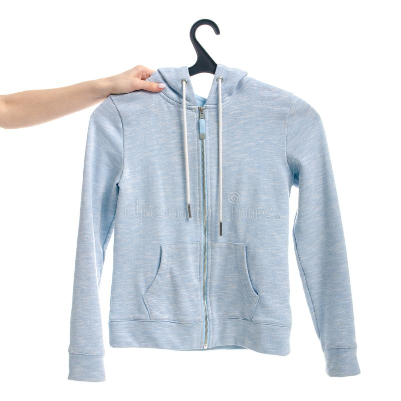 Clothes blue sweatshirt on the lock on a hanger female hand stock photography