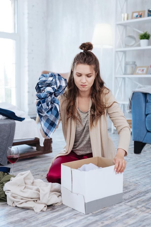 Dark-haired woman putting clothes of ex husband into box. Clothes in box. Dark-haired depressed woman putting all of the clothes of ex husband into big cardboard stock photography