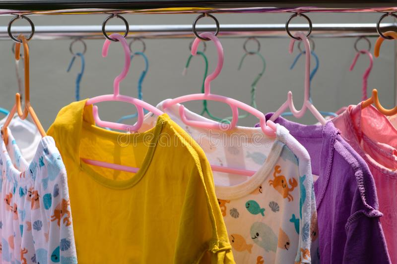 Clothes and children`s dresses in various colors stock images