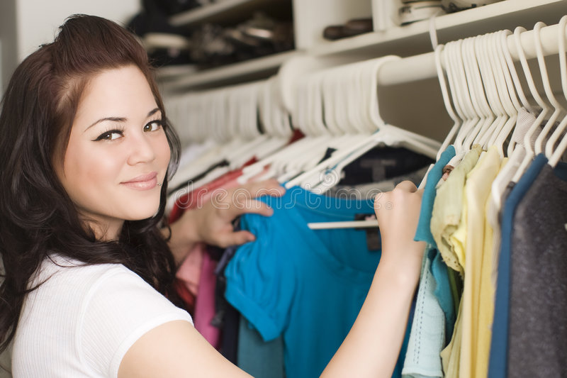 Clothes in closet. Woman looking at clothes in a closet stock photo