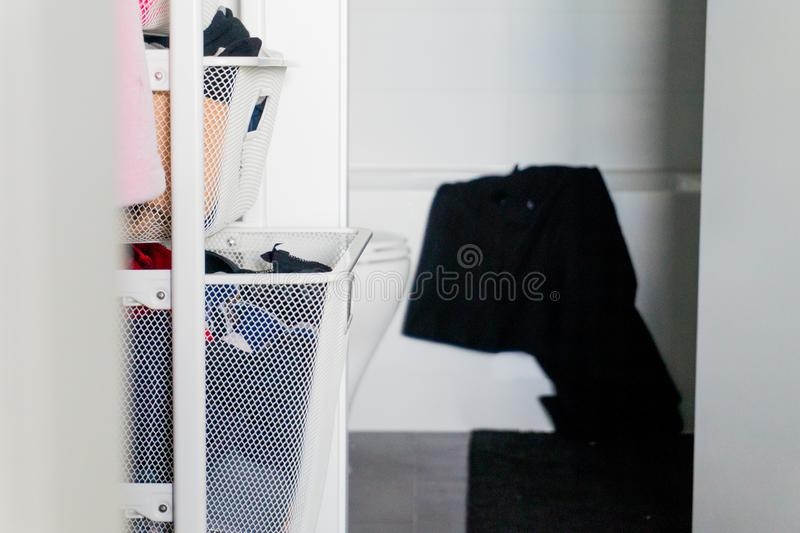 Clothes in closet drawer basket organizers, with bathroom in the background, and black towel hanging over bath tub stock image