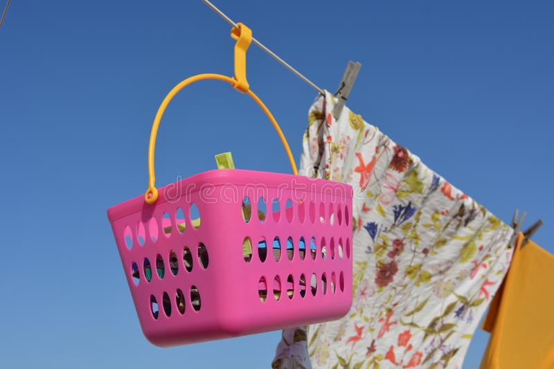 Clothes and clothespins in a pink basket hanging from clothesline stock image