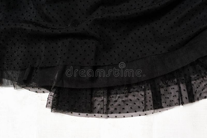 Clothes fashion concept. Detail of black tulle skirt on white wooden background. Top view stock images