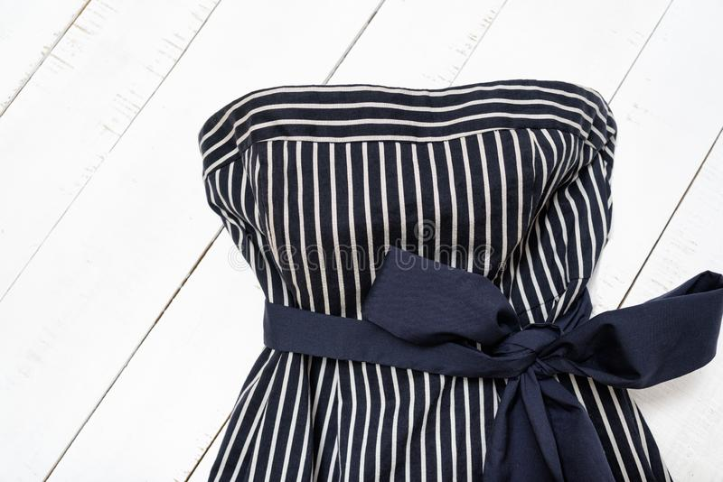 Clothes fashion concept. Detail of blue striped dress with bow on white wooden background. Top view royalty free stock photography