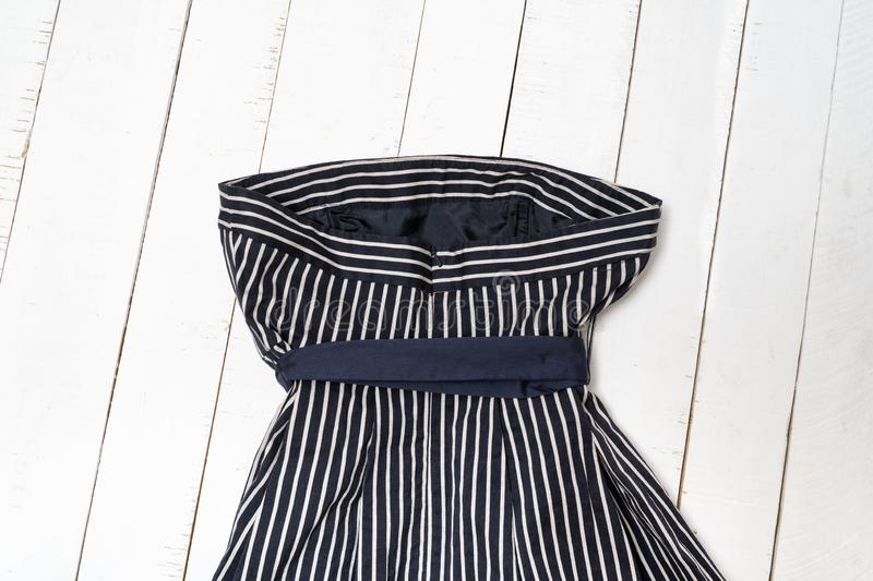Clothes fashion concept. Detail of blue striped dress with bow on white wooden background. Top view royalty free stock photo