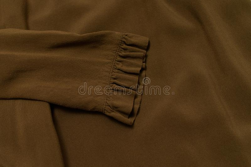 Clothes fashion concept. Sleeve of khaki blouse. Top view royalty free stock photos