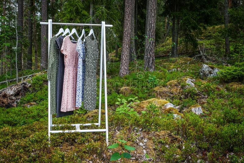 Clothes hanger with dresses in the woods. Concept for organic clothes, eco-friendly, ecological fashion royalty free stock photos