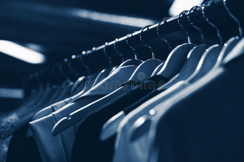 Clothes hangers in fashion store. Clothes business concept. Blue. Selective focused royalty free stock image
