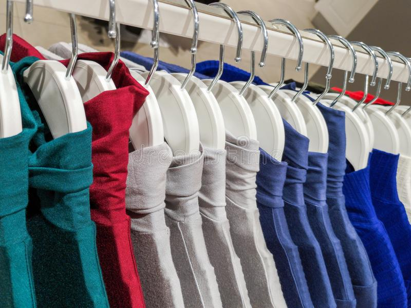 Clothes on hangers in the store. Clothes hang on a shelf in a designer clothing store in different colors royalty free stock images