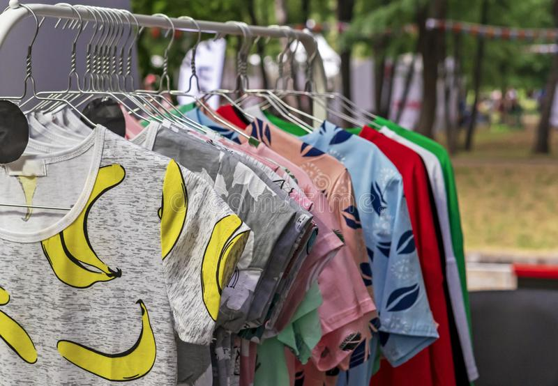 Clothes on hangers in the store. T-shirts on metal hangers royalty free stock images
