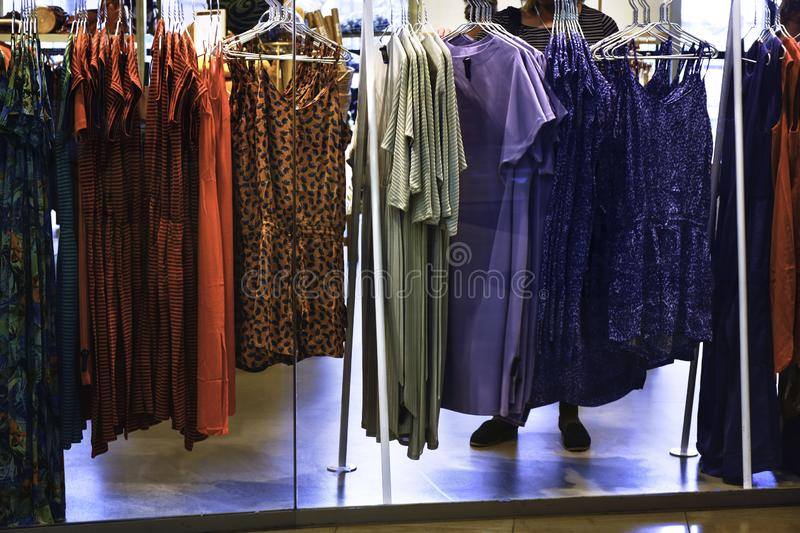 Clothes hanging on the rack in the fashion store. Woman choosing and buying clothes in shopping store stock image