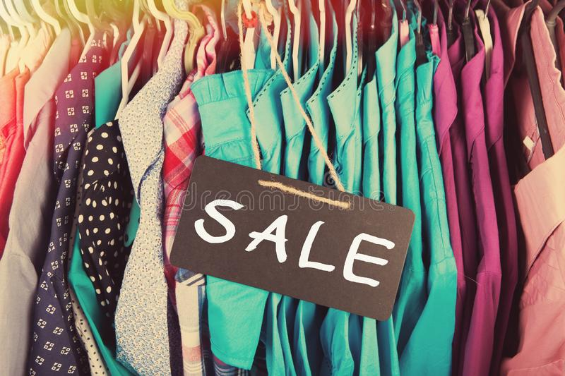 Clothes hanging on the rack in the store. Sale label, Clothes hanging on the rack in the fashion store clothing retail garment collection price shop tag dress stock image