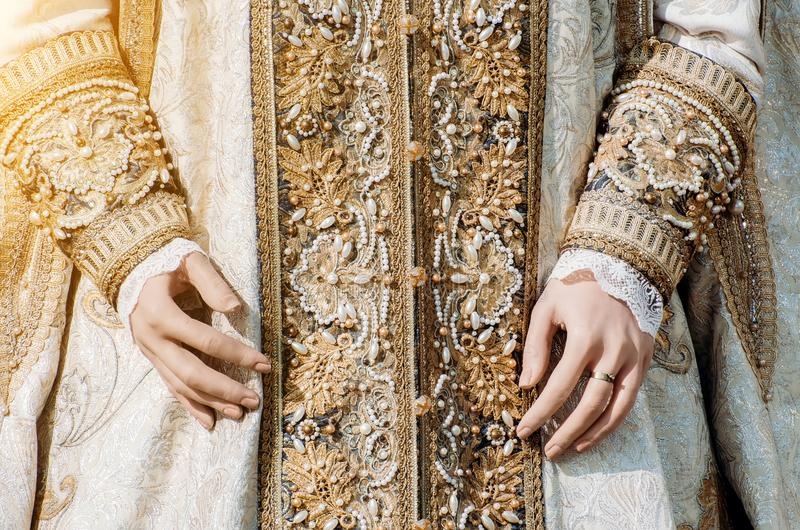 Clothes of a historical imperial woman with pastel tones, hands with a ring with a precious stone stock photo