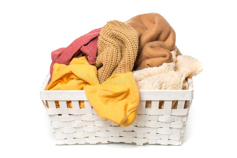Clothes in a laundry wooden basket isolated on white background royalty free stock photography