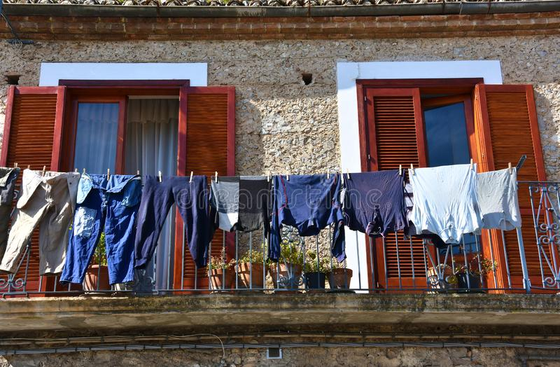 Clothes on a line drying outside. Laundry drying outside at a line between the windows in the old city of Morano Calabro, Calabria stock photos