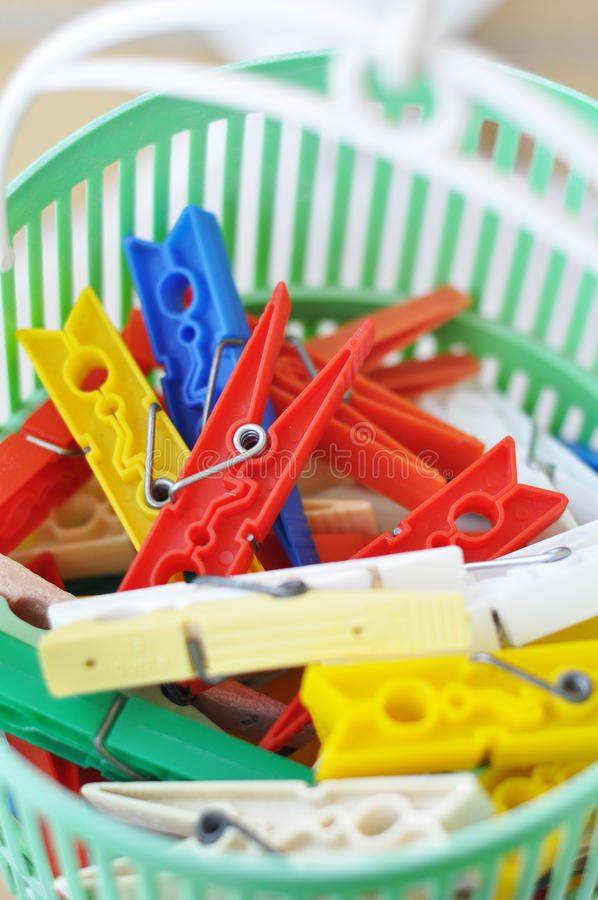 Clothes pegs. Colored clothes pegs in plastic basket closeup stock photos