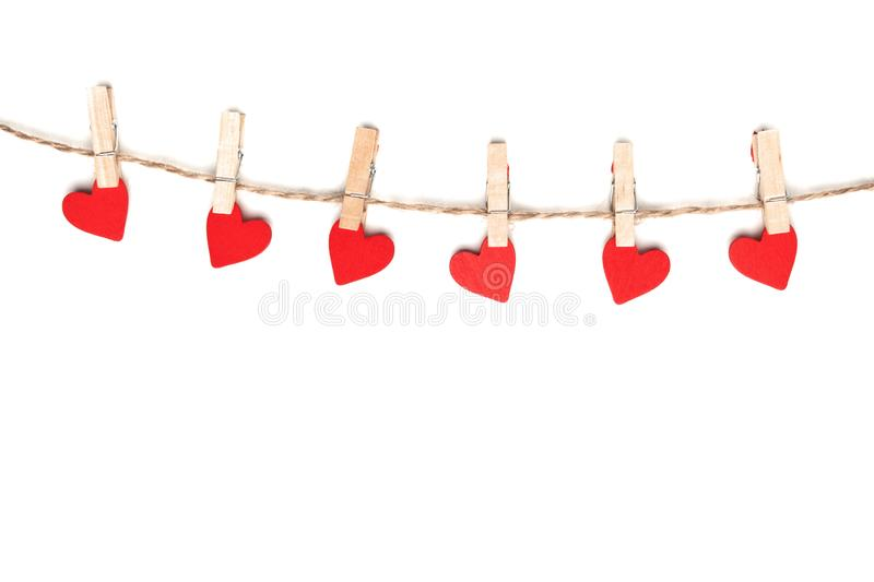 Clothes pegs and red paper hearts on rope isolated on white background royalty free stock photography
