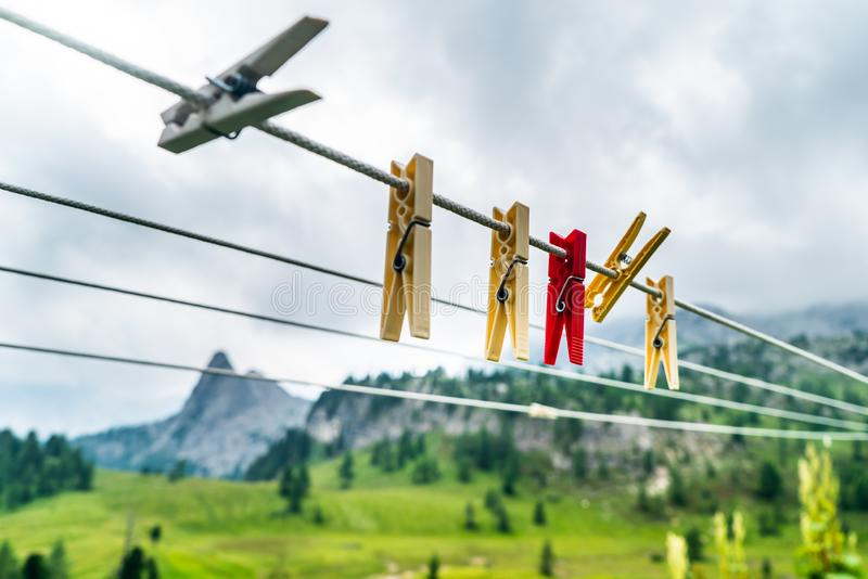 Clothes pins on a clothes line rope. clothespins hanging hook. Clothes pins lined up on a wire. Fresh green meadow and mountains o. N the background. Wooden stock photo