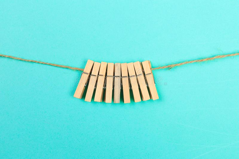 Clothes pins on a clothes line rope - four wooden pegs holding nothing - Image. Clothes pins on a clothes line rope - four wooden pegs holding nothing stock photo