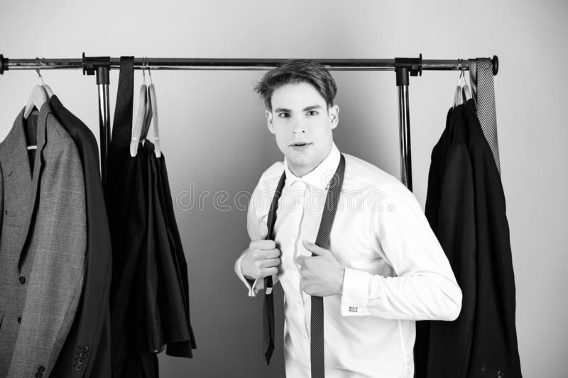 Clothes rack and man in shirt wearing tie on pink background royalty free stock images