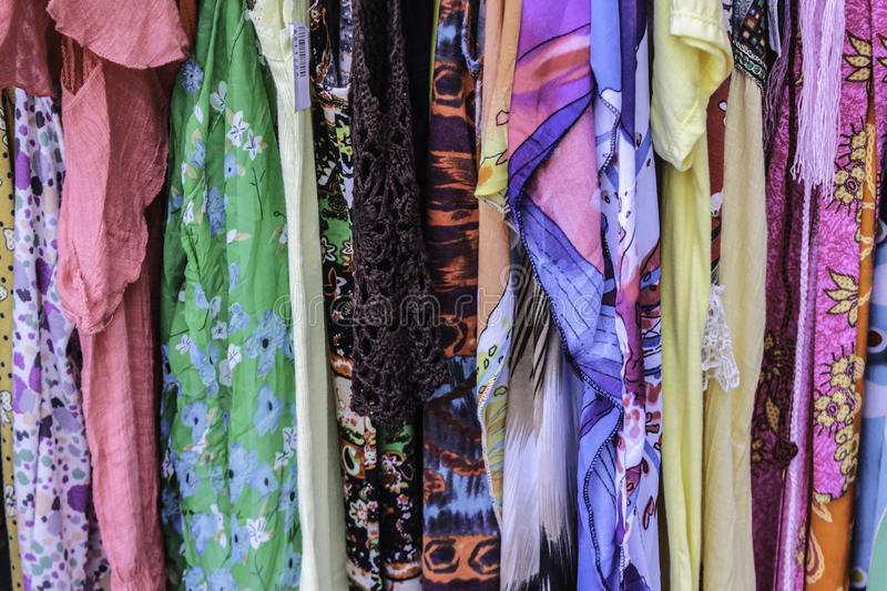 The Clothes Rack. A row of garments hang froma rack for sale stock image