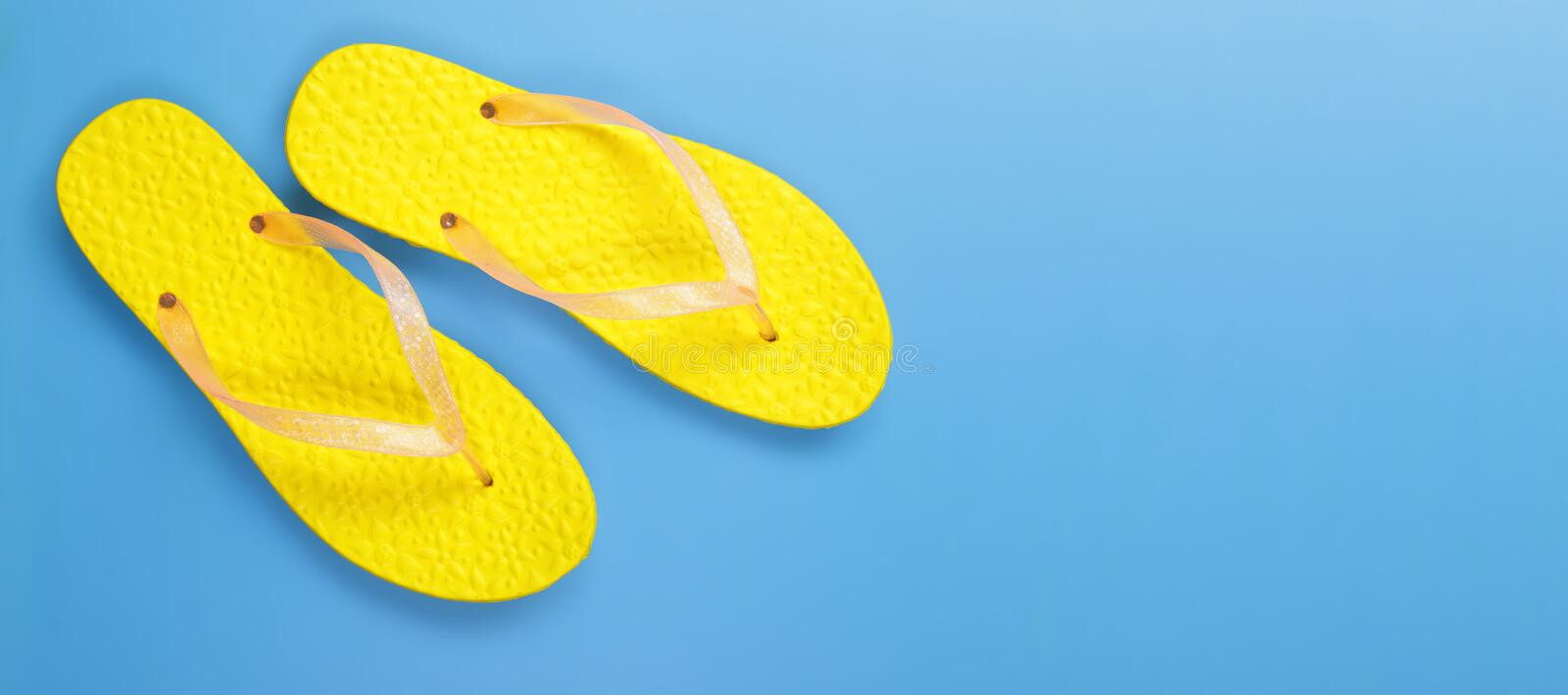 Clothes, shoes and accessories - top view yellow pair flip flops blue background. Clothes, shoes and accessories - top view yellow pair flip-flops sandal on a stock images