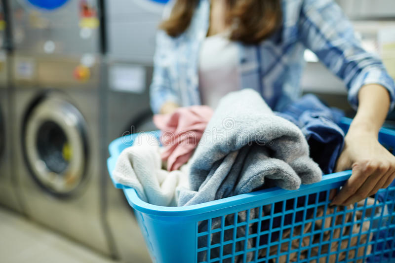 Clothes to wash. Woolen clothes in laundry-basket held by laundress royalty free stock photography