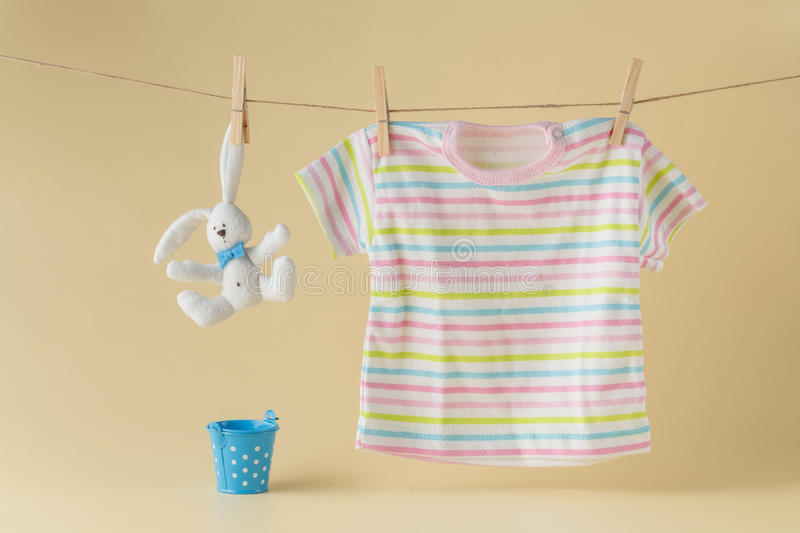 Clothesline with toy doll and baby clothes royalty free stock images