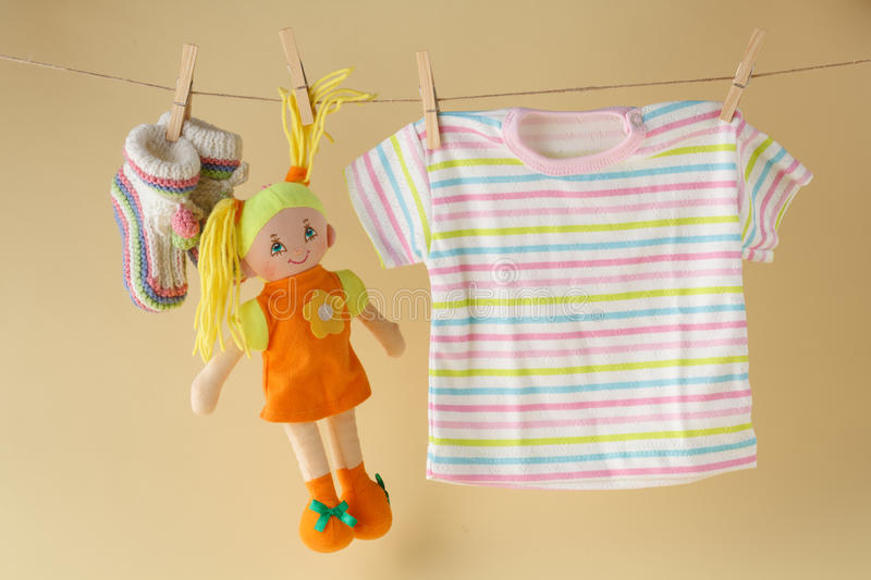 Clothesline with toy doll and baby clothes royalty free stock image
