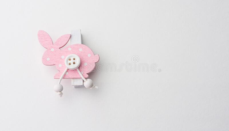 Clothespin-bunny on a sheet of paper for inscription. Wood clothespin-bunny on a sheet of paper for inscription royalty free stock photo