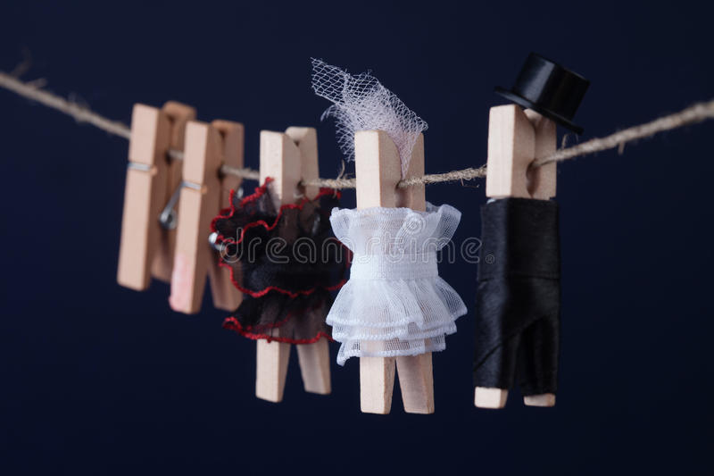 Clothespin characters on dark blue background. Woman in white black dresses, groom character man suit hat. Macro view. Shallow depth of field royalty free stock image