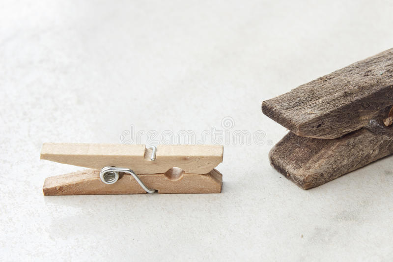 Clothespin contrast. Contrast between small new and big old tweezer clothespin on a textured bright background royalty free stock photo