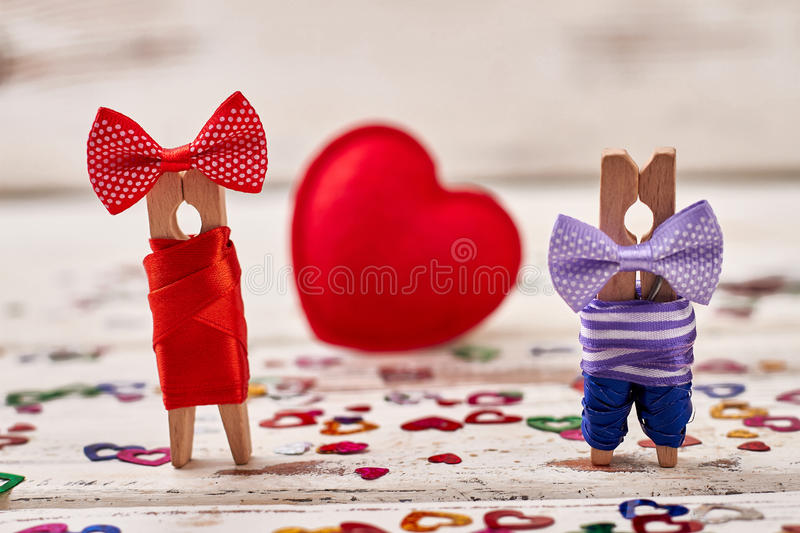Clothespin couple on heart backdrop. Red heart and dressed pegs. Small gesture of big love stock photography