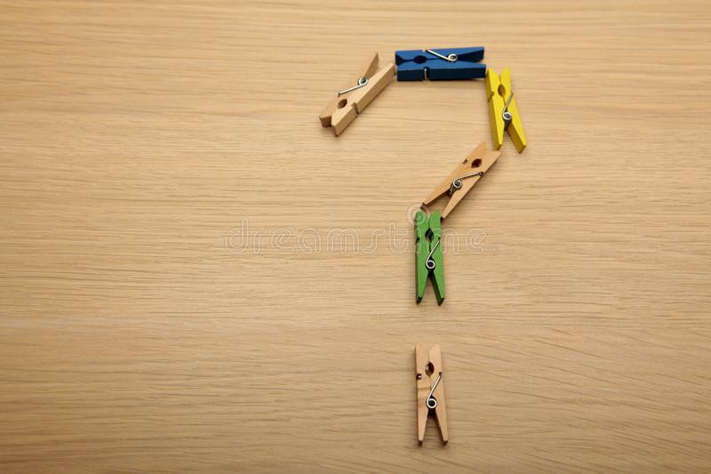 Clothespin question mark wooden table background stock photography