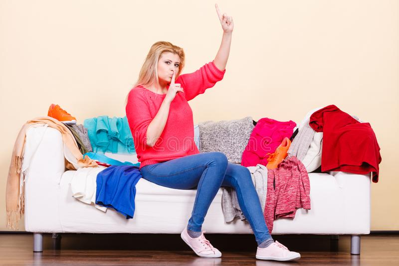 Woman does not know what to wear sitting on couch royalty free stock images