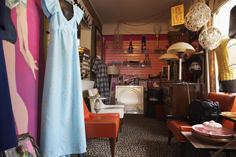 Clothing And Furniture In Second Hand Store. View of clothing and furniture in crowded second hand store stock photography