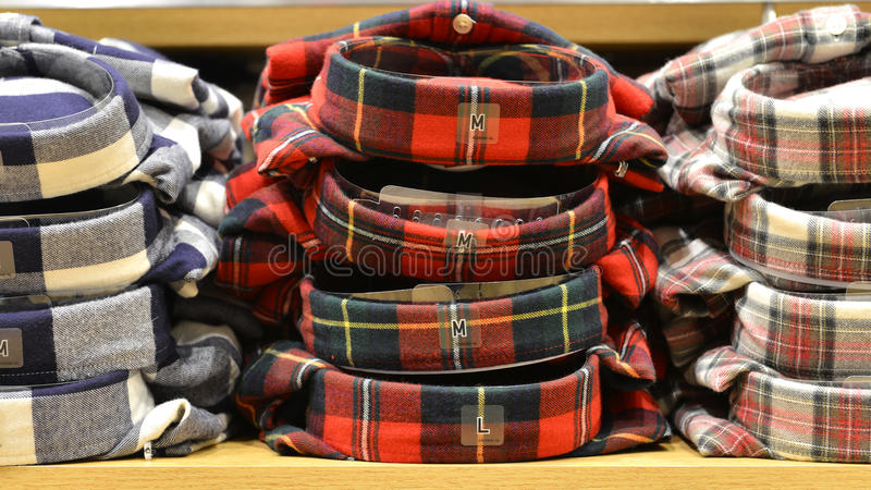 Clothing stacked neatly on the shelf in fashion shop. Close up of plaid clothes stacked neatly on the shelf in fashion shop,Hongkong,China,Asia stock image